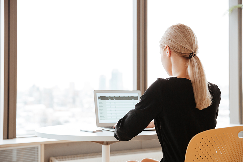 Back view photo of young woman worker using laptop